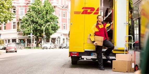 Ein Paketbote liefert ein Paket mit DHL aus