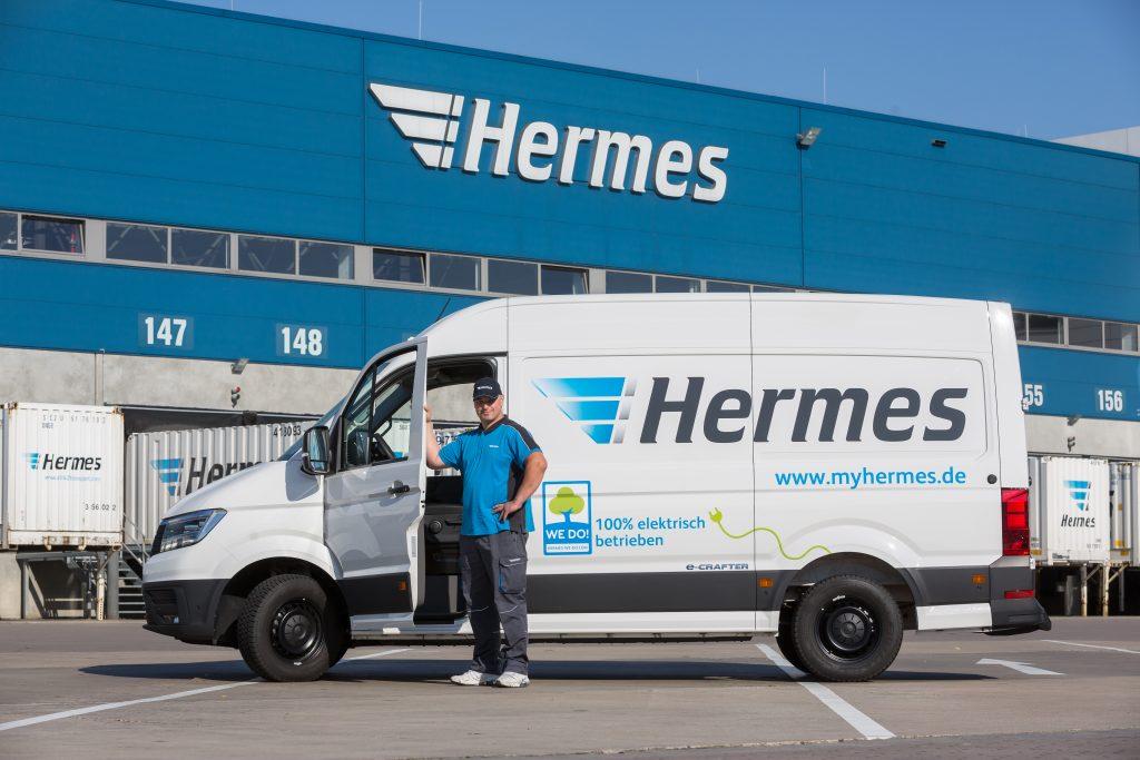 Ein Hermes Paketfahrer vor seinem Zustellfahrzeug